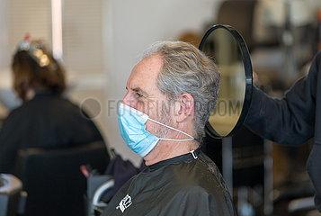 Deutschland  Bremen - Oeffnung der Friseusalons nach der 2. Coronawelle  Kunde betrachtet fertigen Haarschnitt im Spiegel