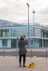 Berlin  Deutschland - Passant fotografiert das Cafe Moskau in der Karl-Marx-Allee