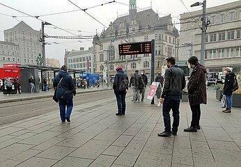 Menschen an einer Strassenbahnhaltestelle