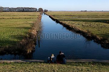 Deutschland  Bremen - Junge Leute sitzen an einem Entwaesserunggraben mit Blick auf das Naturschutzgebiet Hollerland