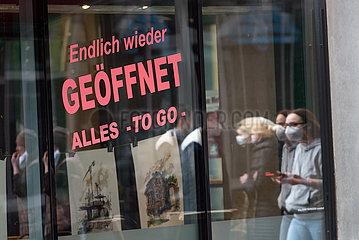 Deutschland  Bremen - Hinweis auf Oeffnung im Schaufenster eines Geschaefts in Coronazeiten