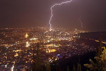 Tiflis  Georgien  Blick ueber die Stadt in der Nacht bei Gewitter mit Blitzeinschlag
