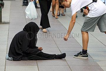 Tiflis  Georgien  Junge gibt einer Bettlerin Geld