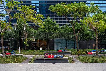 Singapur  Republik Singapur  Eine Gruppe suedasiatischer Arbeitsmigranten ruht sich auf Baenken in Marina Bay aus