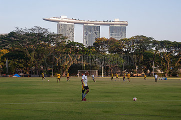 Singapur  Republik Singapur  Menschen spielen auf dem Padang Field Fussball mit dem Marina Bay Sands Hotel im Hintergrund