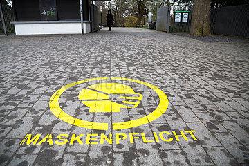Deutschland  Hamburg - Hinweis auf Maskenpflicht vor Eingang zu einem Park beim Dammtor