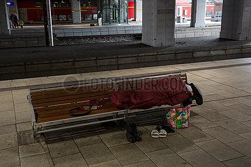 Deutschland  Hamburg - Obdachloser schlaeft in Coronazeiten auf einer Bank im Hamburger Hauptbahnhof
