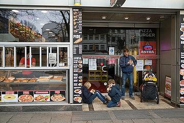 Deutschland  Hamburg - Reeperbahn  Stadtteil St.Pauli in der Corona-Tristesse  Familie isst Doener im Eingangsbereich  weil kein Zutritt wegen Corona