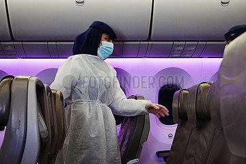 Frankfurt am Main  Deutschland  Flugbegleiterin geht waehrend der Coronapandemie in einer Flugzeugkabine mit Mund-Nasen-Schutz durch die leeren Sitzreihen