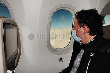 Riad  Saudi-Arabien  Mann mit Mund-Nasen-Schutz schaut aus einem Flugzeugfenster