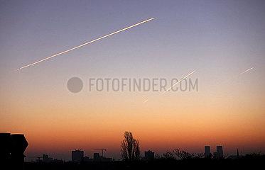 Berlin  Deutschland  Flugzeuge hinterlassen bei Daemmerung Kondensstreifen am Himmel
