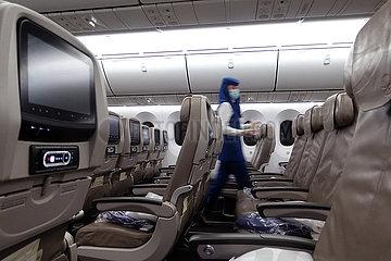 Riad  Saudi-Arabien  Flugbegleiterin geht waehrend der Coronapandemie in einer Flugzeugkabine mit Mund-Nasen-Schutz durch die leeren Sitzreihen