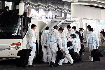 Frankfurt am Main  Deutschland  Auswirkungen der Coronapandemie: Flugpassagiere stehen in Schutzanzuegen vor dem Terminal des Flughafen neben einem Reisebus