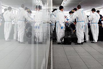 Frankfurt am Main  Deutschland  Auswirkungen der Coronapandemie: Flugpassagiere stehen in Schutzanzuegen vor dem Terminal des Flughafen