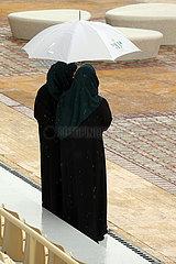 Riad  Saudi-Arabien  einheimische Frauen stehen bei Schlechtwetter unter einem Regenschirm