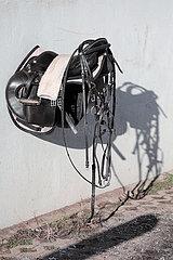 Bruchmuehle  Sattel und Zaumzeug haengt an einer Stallmauer