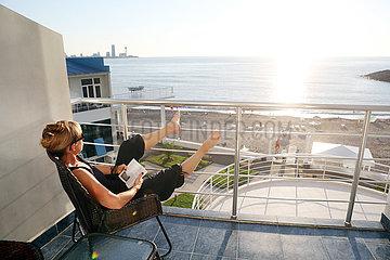 Batumi  Georgien  Frau sitzt auf dem Balkon eines Hotels und schaut in die Ferne