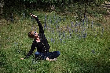 Dranse  Deutschland  Frau sitzt im Gras und dehnt sich
