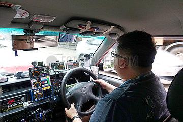 Hong Kong  China  Taxifahrer hat zahlreiche Smartphones an seinem Armaturenbrett