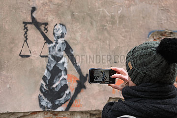 Krakau  Polen  Frau fotografiert mit ihrem Smartphone eine Malerei der Justitia an einer Hauswand