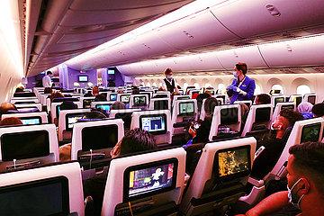 Dubai  Vereinigte Arabische Emirate  Flugbegleitende gehen waehrend der Coronapandemie in einer Flugzeugkabine mit Mund-Nasen-Schutz durch die Sitzreihen