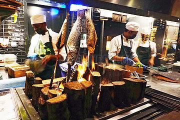 Dubai  Vereinigte Arabische Emirate  Koeche bereiten Fisch ueber offenem Feuer zu