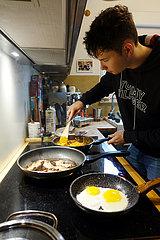 Berlin  Deutschland  junger Mann beim Kochen