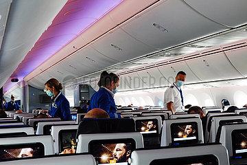 Amsterdam  Niederlande  Flugbegleitende gehen waehrend der Coronapandemie in einer Flugzeugkabine mit Mund-Nasen-Schutz durch die Sitzreihen