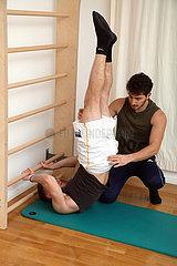 Berlin  Deutschland  Physiotherapeut unterstuetzt einen Patienten bei einer Uebung an einer Sprossenwand