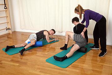 Berlin  Deutschland  Physiotherapeutin unterstuetzt einen Patienten bei einer Uebung auf einer Gymnastikrolle