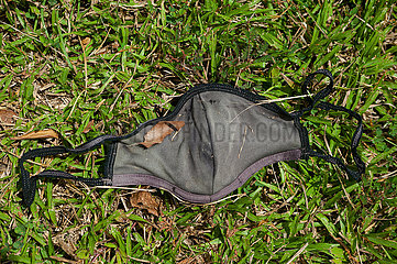 Singapur  Republik Singapur  Benutzter Mundschutz gegen Corona (Covid-19) liegt auf dem Boden im Gras