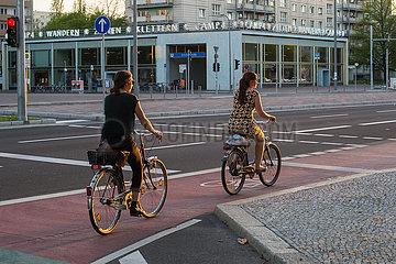 Berlin  Deutschland - Fahrradfahrerinnen im Sonnenuntergang in der Karl-Marx-Allee