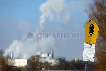 Schwedt  Deutschland  Schild Nationalpark. Im Hintergrund entweichen Abgase aus Schloten der Papierfabrik Leipa Georg Leinfelder GmbH