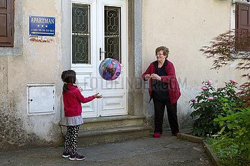 Kroatien  Labin - das malerische  altertuemliche Bergstaedtchen Labin: Grossmutter spielt Ball mit ihrer Enklin
