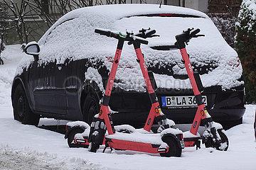 Berlin  Deutschland  E-Roller des Anbieters voiscooters stehen mit Schnee bedeckt auf einer Strasse