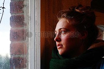 Briescht  Deutschland  junge Frau schaut nachdenklich aus einem Fenster