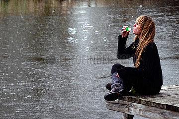 Briescht  Deutschland  Frau sitzt bei Regen an einem See und blaest Seifenblasen in die Luft
