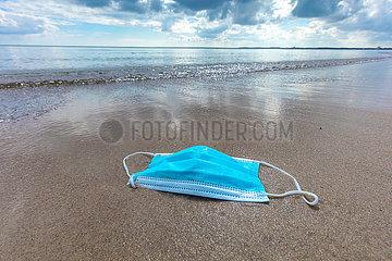 Schutzmaske liegt am Strand