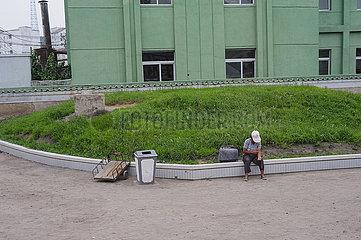 Kaesong  Nordkorea  Alltagsszene mit einer Frau am Strassenrand und Gebaeuden