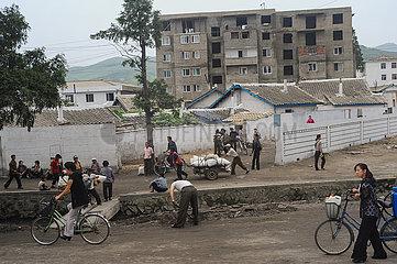 Wonsan  Nordkorea  Alltaegliche Strassenszene mit Menschen und Wohngebaeuden