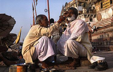 Varanasi  Indien  Barbier rasiert einen Mann an einem Ghat am Ufer des Ganges