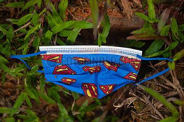 Singapur  Republik Singapur  Benutzter Corona-Mundschutz mit Superman-Muster liegt auf der Erde