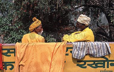 Rishikesh  Indien  Baertige Maenner mit Turban sitzen auf einer Bank und unterhalten sich
