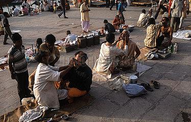 Varanasi  Indien  Barbiere rasieren Maenner an einem Ghat am Ufer des Ganges