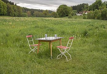 Tisch und Stuehle mitten in der Landschaft  bei Glonn  Bayern  Mai 2021