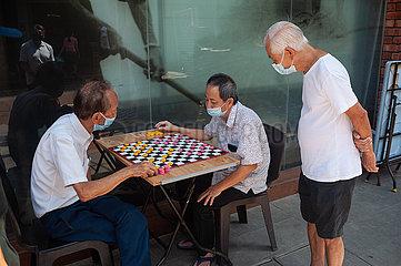 Singapur  Republik Singapur  Maenner spielen waehrend der Coronakrise Chinesisches Schach in Chinatown