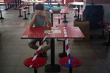 Singapur  Republik Singapur  Mann sitzt waehrend der Coronakrise an einem abgesperrten Tisch in Chinatown