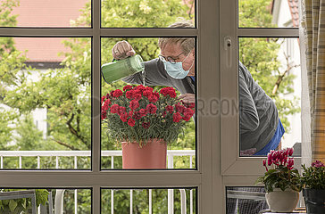 Mann giesst Blumen auf dem Balkon  mit Maske  2021