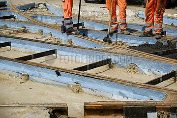 Deutschland  Bremen - Bauarbeiter verteilen Spezialbeton zwischen den neuen Strassenbahnschienen