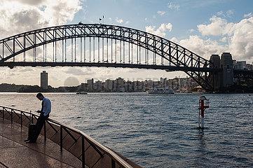 Sydney  Australien  Mann steht am Ufer und surft auf seinem Handy mit der Sydney Harbour Bridge im Hintergrund